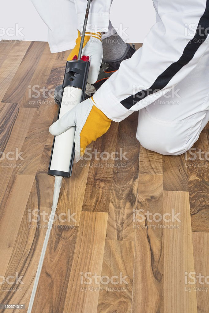 Appling silicone sealant in spaces of old wooden floor stock photo