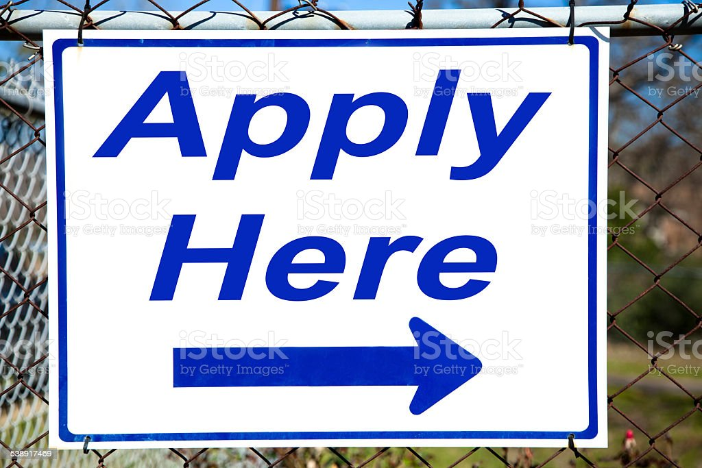 Apply Here Sign hanging on chain link fence stock photo