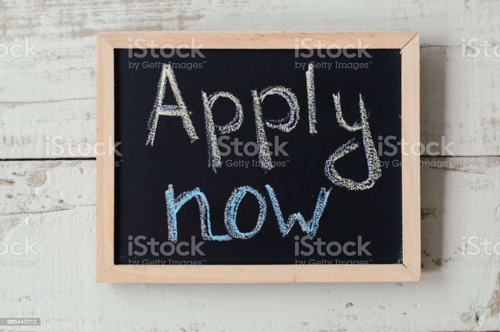 Apply now concept. Balckboard with handwritten text on wooden background. Employment and application process royalty-free stock photo