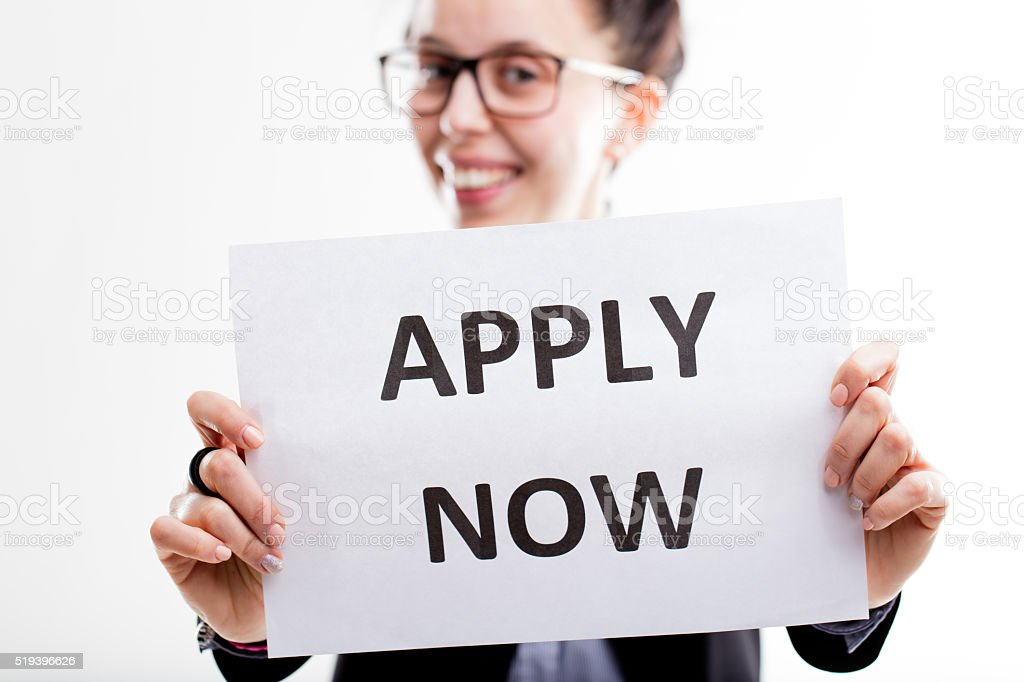 apply now sign hold by a young smiling woman stock photo