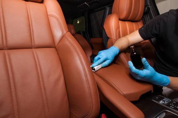一名戴著藍色手套的工人用海綿和瓶子在汽車座椅棕色內飾的皮革上塗上納米陶瓷塗層圖像檔