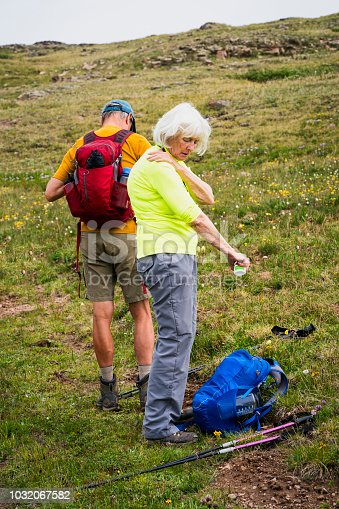 A senior couple apply bug repellent during a hike in the Weminuche Wilderness,  Continental Divide, San Juan National Forest, Rocky Mountains, Silverton, CO, USA