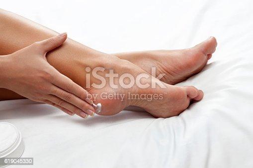 istock applying cream on feet 619045330