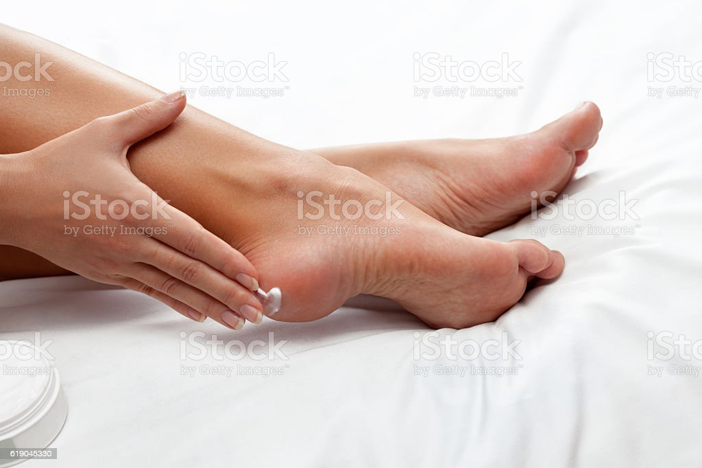 applying cream on feet stock photo