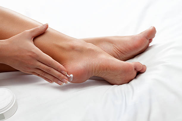applying cream on feet - human foot stock photos and pictures