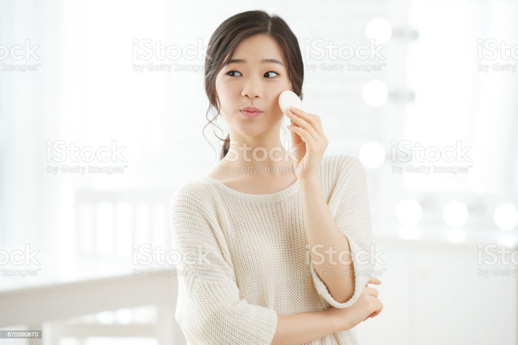 Applying face lotion stock photo