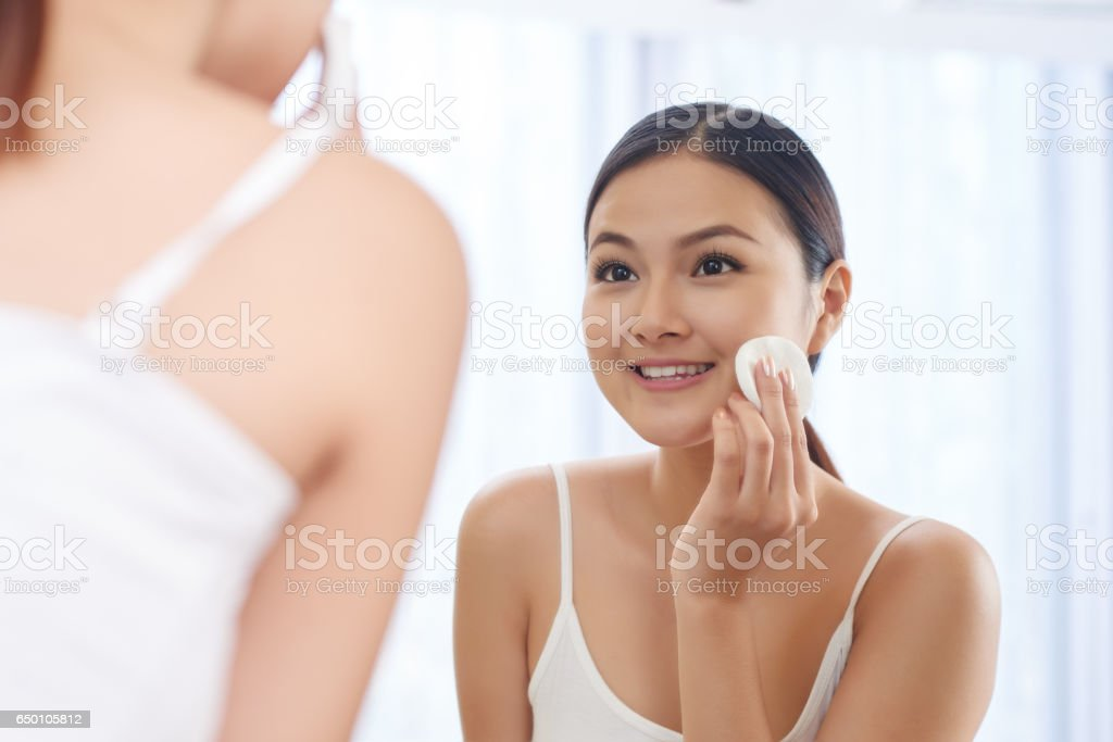Applying face toner stock photo