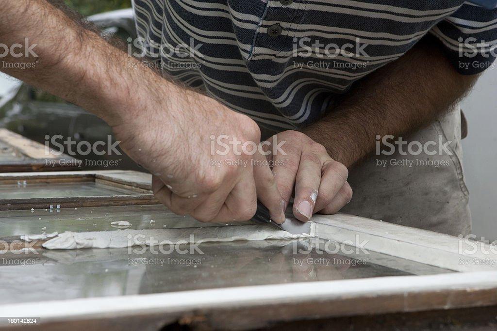 Applying glazing to old window. royalty-free stock photo