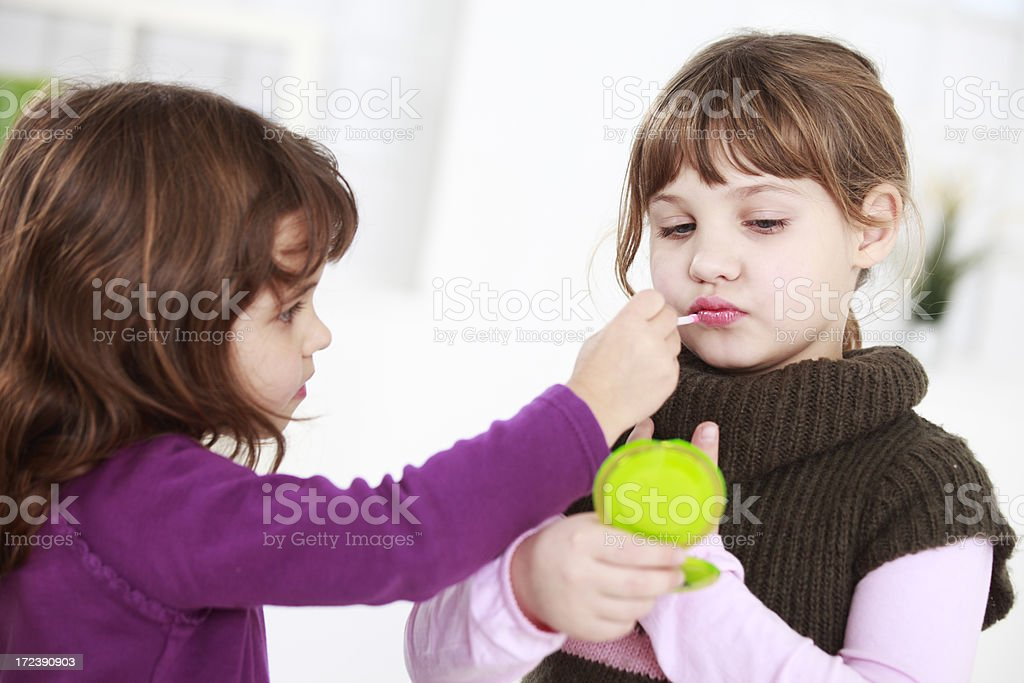Applying lipstick to sister royalty-free stock photo