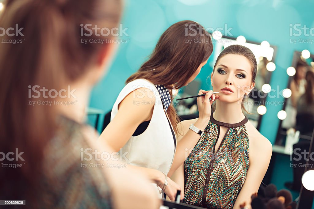 Applying lipstick with a brush stock photo