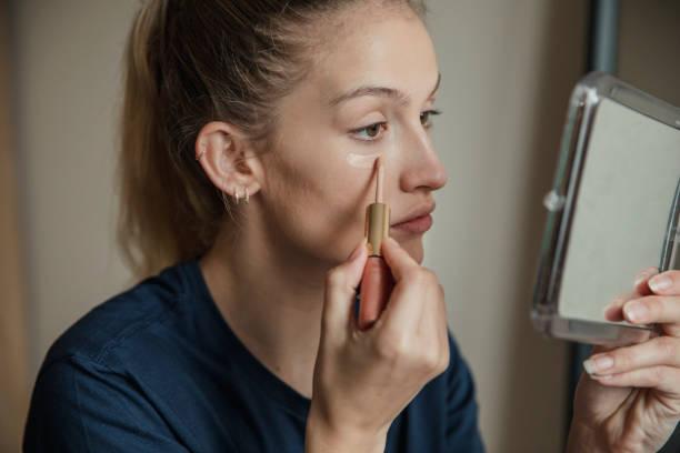 applying make-up to under her eyes - woman make up imagens e fotografias de stock