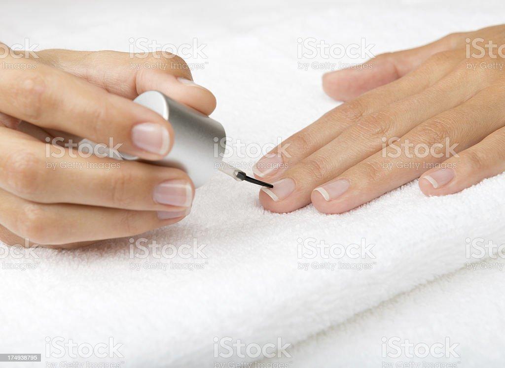 Natural groomed hands applying Nail polish to harden Nails. Nikon...