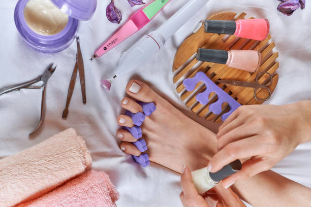 Applying pedicure to woman's feet with white toenails, with toe separators stock photo