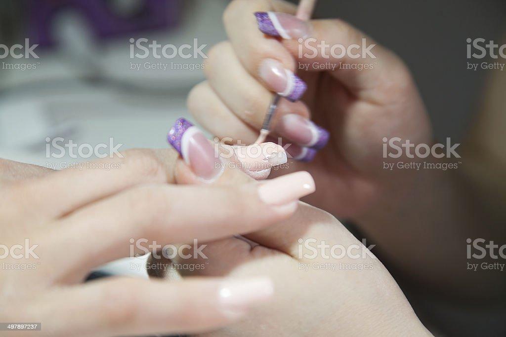 applying pink fingernail polish royalty-free stock photo