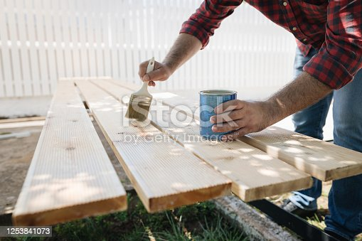 Applying protective varnish on a wooden boards.