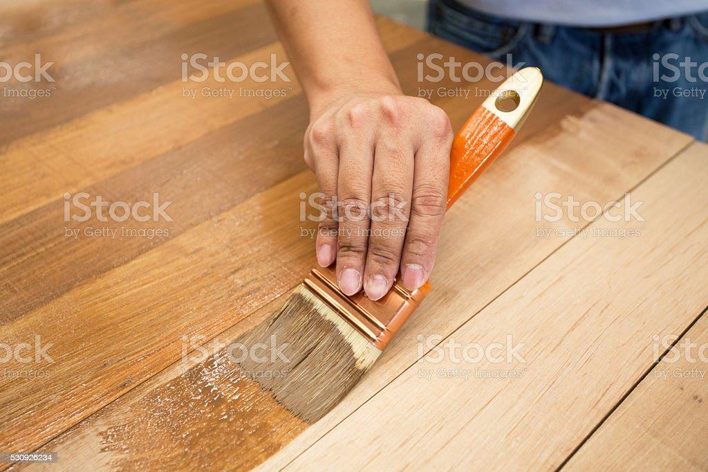 Applicazione di vernice protettiva su un arredamento in legno