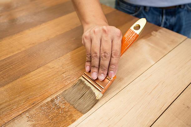 applying protective varnish on a wooden furniture - houtbeits stockfoto's en -beelden