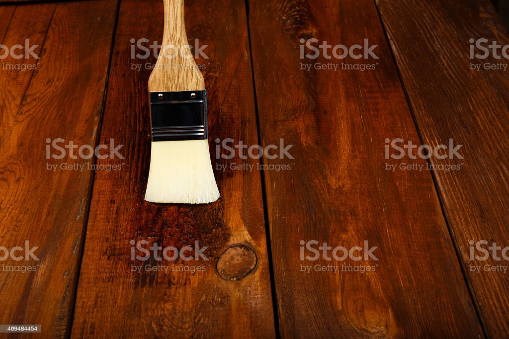 Applying protective varnish on a wooden table stock photo