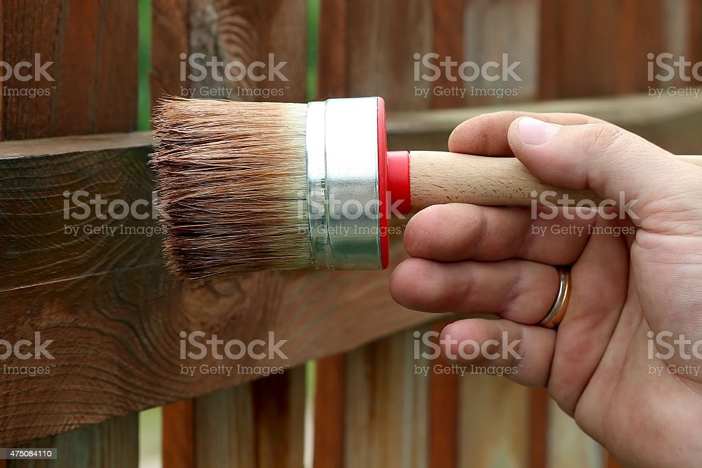 Applying protective varnish to a wooden fence stock photo