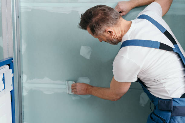 Applying putty to the gypsum plasterboards stock photo