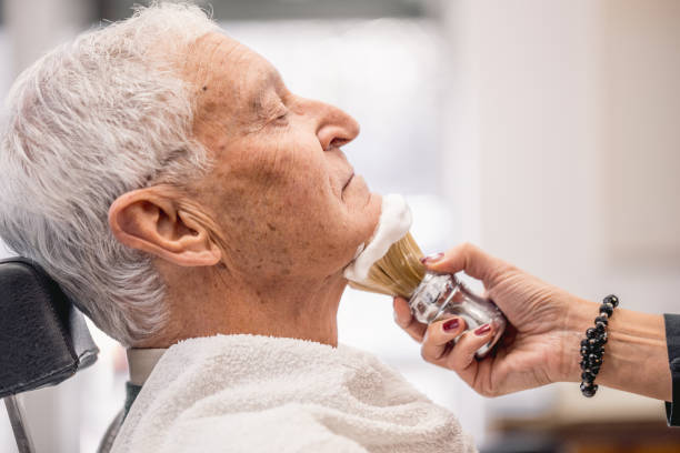 Applying Shaving Cream on Senior Man Side View Applying Shaving Cream on Senior Man, Eyes Closed, Side View shaving brush shaving cream razor old fashioned stock pictures, royalty-free photos & images