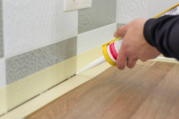 applying silicone sealant with construction syringe. worker fills seam between the ceramic tiles on the wall and kitchen worktop - silicone foto e immagini stock