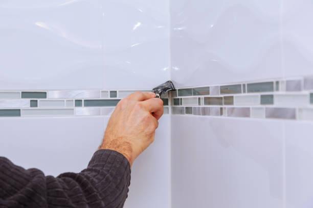 die anwendung von silikondichtmittel mit bauarbeiter füllt die keramikfliesen auf der wandbadezimmeranlage - fugen reinigen stock-fotos und bilder