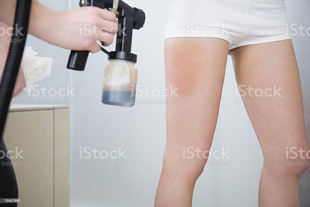 Applying spray tan stock photo