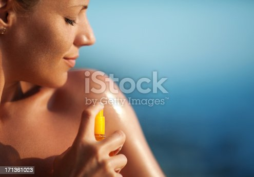Closeup of adult caucasian woman spraying suntan lotion onto her shoulder. It's sunny summer day and she's sunbathing with a smirk on her face. Blurry sea in background.