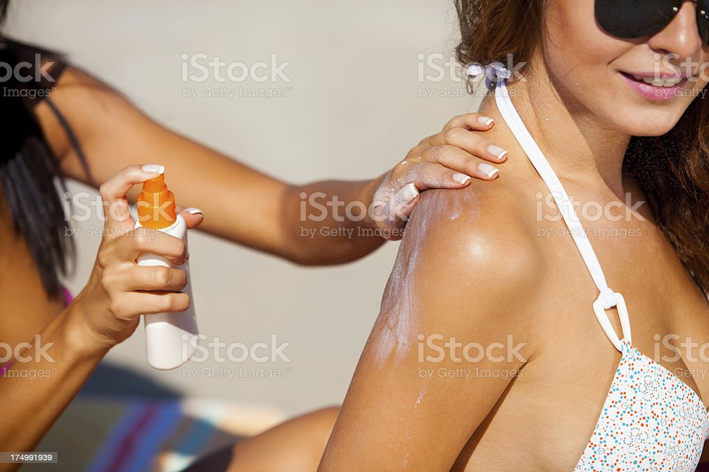 Applying suntan lotion stock photo
