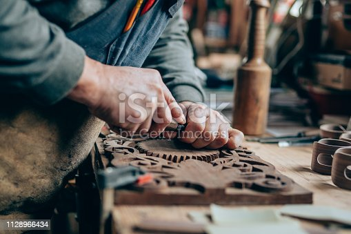 Close up of a carpenter hands working with a chisel and carving tools