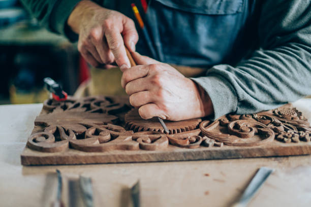 Applying the finishing touches Carpenter hands working with a chisel and carving tools carving craft activity stock pictures, royalty-free photos & images