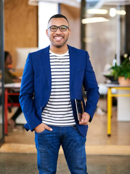 Applying the lens of efficiency to all aspects of business Shot of a handsome young designer standing in his office design occupation stock pictures, royalty-free photos & images