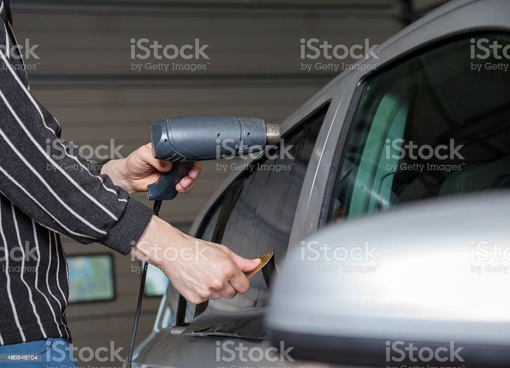 Applying tinting foil on a car window stock photo