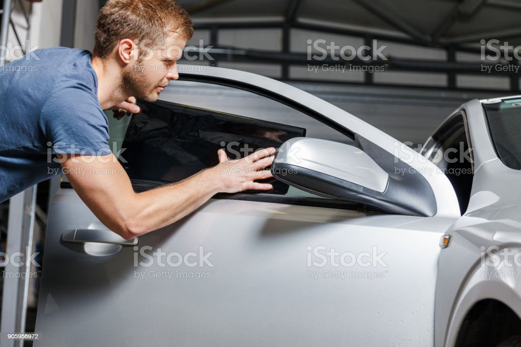 Applying tinting foil onto a car window – zdjęcie