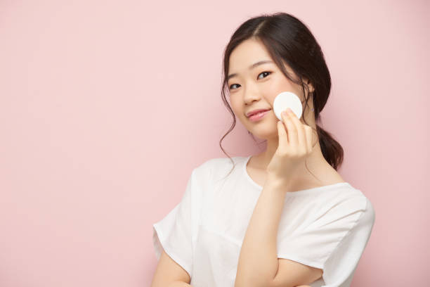 Applying toner Lovely Korean woman applying toner on her skin korean ethnicity stock pictures, royalty-free photos & images