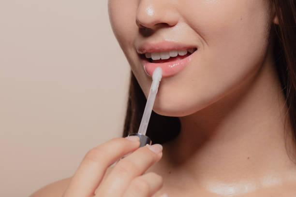 anwendung von transparenten lipgloss - menschlicher mund stock-fotos und bilder