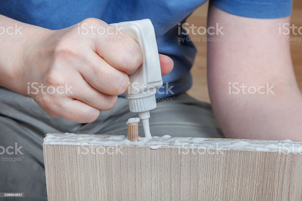 Applying wood glue, carpenter gluing wooden parts for furniture, stock photo