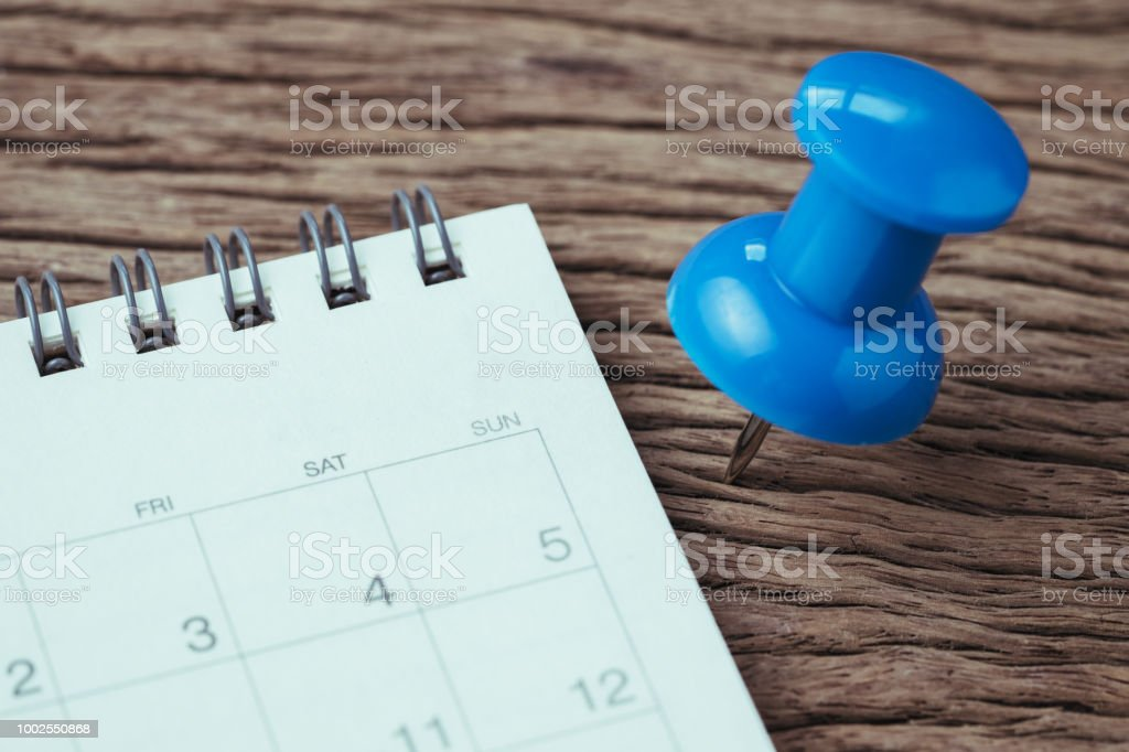 Appointment, deadline, holiday or date planning concept, big blue pushpin or thumbtack pin on wooden table next to white clean calendar stock photo