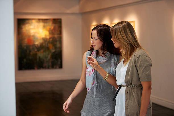 Appreciating art Two young woman examining a painting up close while attending an exhibitionhttp://195.154.178.81/DATA/i_collage/pi/shoots/781126.jpg critic stock pictures, royalty-free photos & images