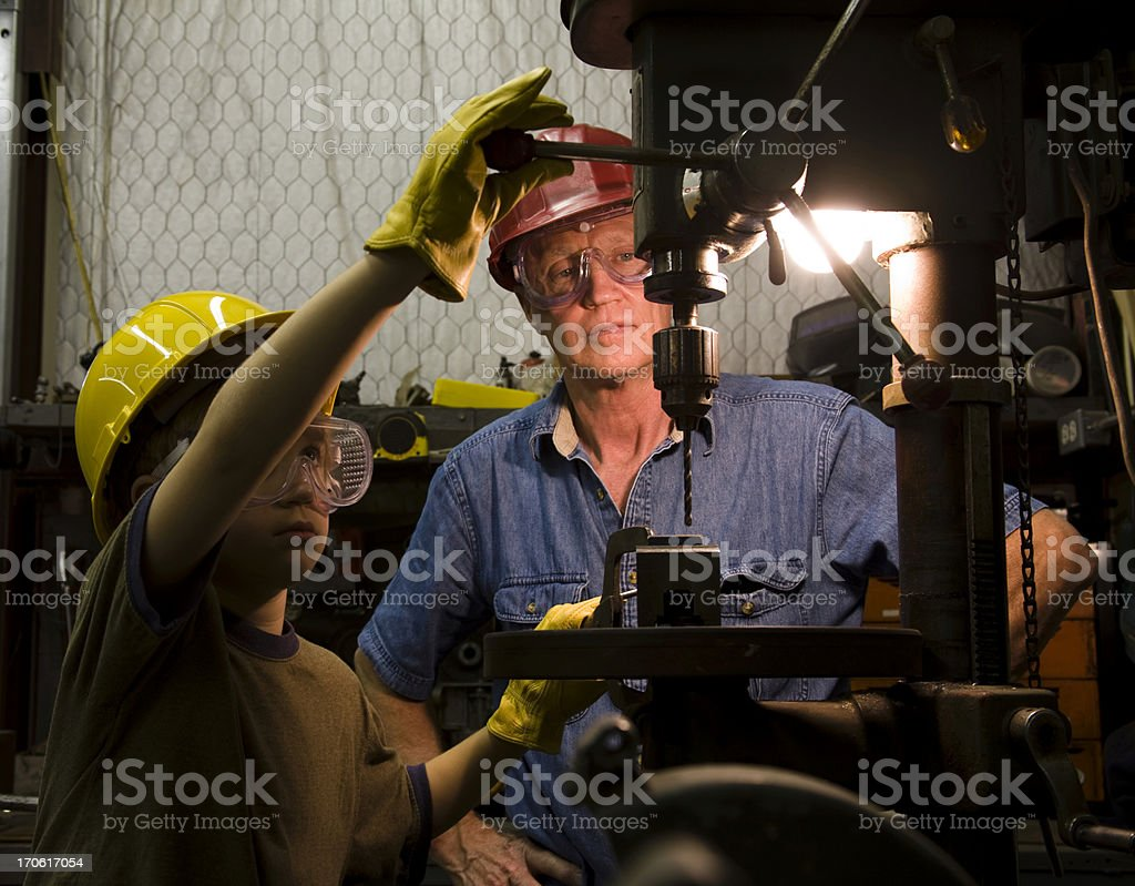 Apprentice at work. Young boy learning from grandfather.  Workshop. stock photo