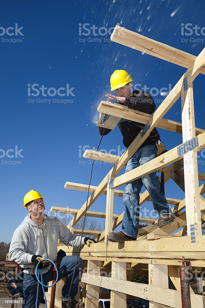 Apprentice Carpenter Building House With Supervision royalty-free stock photo