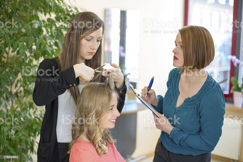 Apprentice cutting hair while instructor is watching stock photo