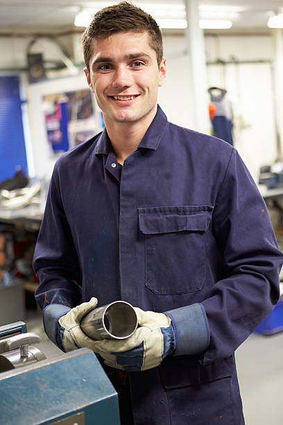 Apprentice Engineer Working On Factory Floor stock photo