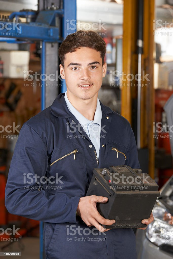 Apprentice Mechanic Holding Car Battery In Auto Repair Shop stock photo