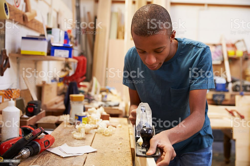 Apprentice Planing Wood In Carpentry Workshop stock photo