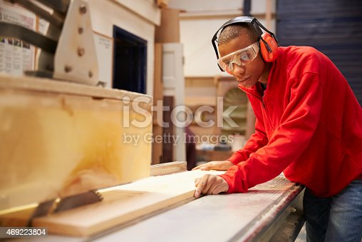 istock Apprentice Using Circular Saw In Carpentry Workshop 469223804