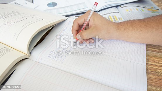 Approach to a human hand writing: BANCOS, CUENTAS POR COBRAR, CUENTAS POR PAGAR - BANKS, ACCOUNTS RECEIVABLE, ACCOUNTS PAYABLE in Spanish language - a list of expenses in a ledger on wooden table