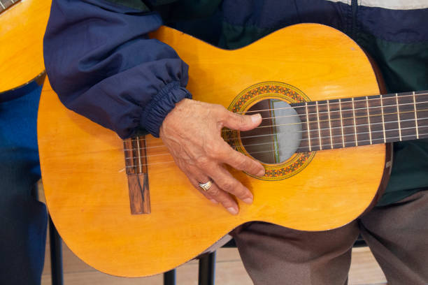 Approach to the hand of an elderly man sitting holding a guitar dressed in a blue shirt with a ring on his finger Approach to the hand of an elderly man sitting holding a guitar dressed in a blue shirt with a ring on his finger serenading stock pictures, royalty-free photos & images