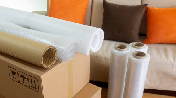 approach to three rolls of cardboard, foam and bubble wrap used to pack things on a cardboard box with a sofa in the background - alejomiranda stock pictures, royalty-free photos & images